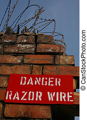 Razor Wire 02 - A danger sign warning of the empacement of...