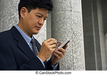 Getting Organized - Asian man in a business suit with a PDA