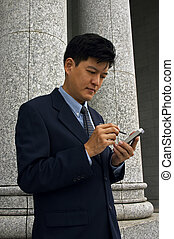 Man With PDA - Asian man in a business suit with a PDA...