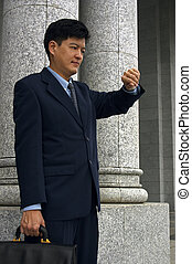 Appointment - Asian man in a business suit standing outside...