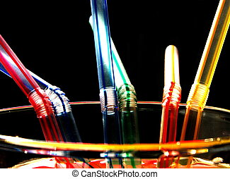 six coloured straws - straws on a glass - coloured, on black...