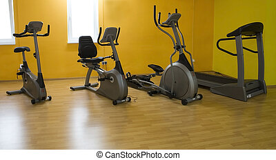 fitness equipment - a row of fitness equipment in a gym