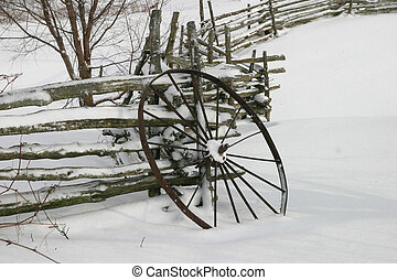 Winter Wheel - An old iron wagon wheel propped up against a...