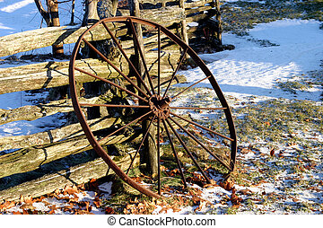 Rusty Wheel - Old rusty iron wheel leaning against a wood...