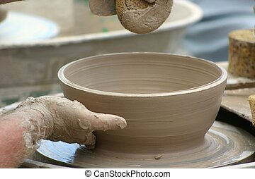 Potter at Work - Pottery bowl being shaped on potter's wheel