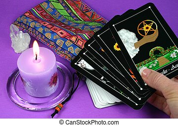 Tarot Cards in hand - Hand holding tarot cards with deck and...