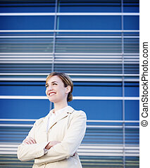 Business woman standing with smile in front of a modern...
