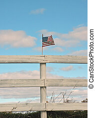 flag on the fence - flag on a farms fence with sky in the...