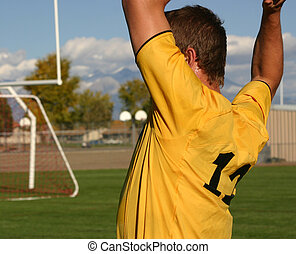 Throw In - Soccer player throwing the ball back onto the...