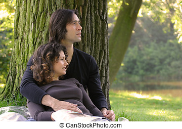 Loving couple - Attractive young couple outdoors leaning...