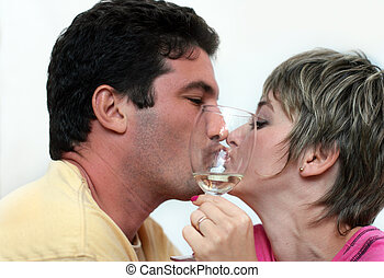 Kissing couple with a glass of wine