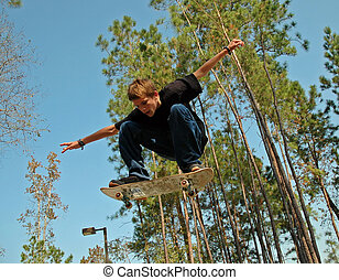 Airborne Teen Skate - A teenaged skateboarder soars through...