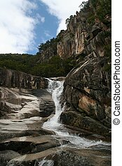Waterfalls - A waterfall runs down the side of cliff in...