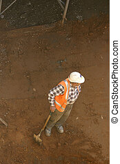 Builder and shovel - A workman leans on his shovel in a dirt...