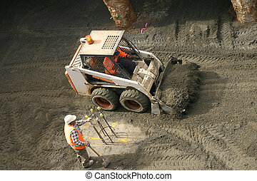 Bobcat and construction worker - A bobcat shovels gravel...