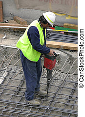 Jackhammer - A workman using a jackhammer Focus is to the...