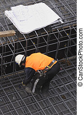 Builder and Site Plans - A builder secures steel mesh...
