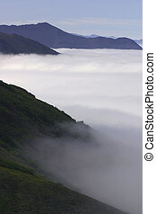 Peaceful Mountains - Mountains shrouded in mist provide a...