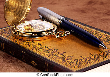 Book and Watch - Photo of a Book and a Pocket Watch.
