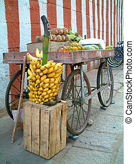 banana and cart - a fruit cart with bunch of bananas infront