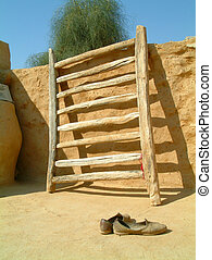 Indian village courtyard with shoes and a ladder