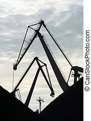 cranes - Crane silhouettes in a harbour Piles of coal in...