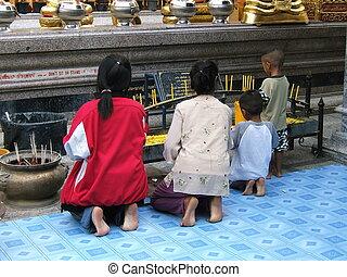 Praying Buddha - Two women, one girl and one boy praying...