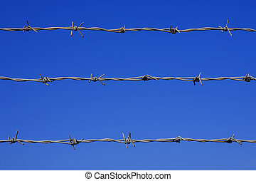 Barbed wire fence detail, against a blue sky with space for...
