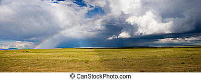 storm panorama - A rainstorm, complete with half rainbow,...
