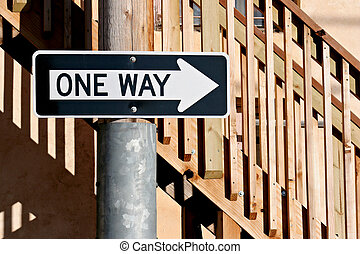 one way sign infront of some stairs in an alley