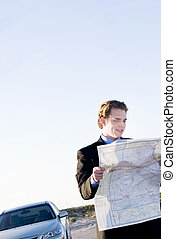 business man lost - young businessman consults map because...