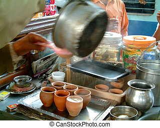 serving chai tea - man serving boiling chai tea in clay...