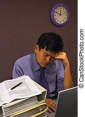 Headache at Work - An employee under stress with a headache...