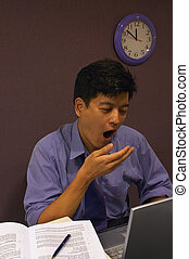 Exhausted! - A man working late into the night yawns at his...