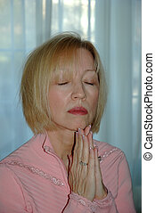 Woman Praying - Woman praying with her hands folded in front...