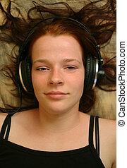 Enjoying music 1 - A teenager with headphones lying on a...