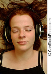 Enjoying music 2 - A teenager with headphones lying on a...
