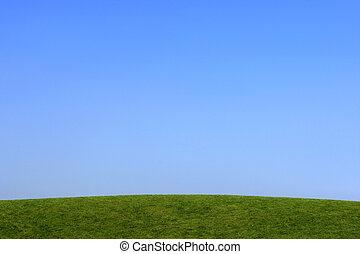 Simple Skyline - Grass hillside with a clear blue sky.