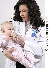 Medicating Baby - A doctor medicates a baby using a measured...