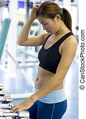 Which Weight? - A female fitness enthusiast looks confused...