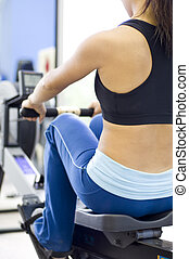 Rowing Machine - A female fitness instructor uses a rowing...