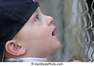 cute kid looking up in awe - cute young boy standing by a...