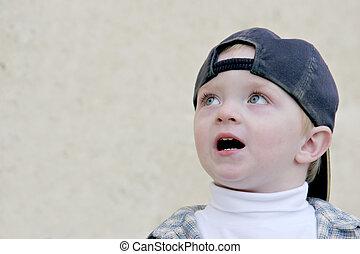 cute boy surprised - cute young boy wearing a baseball cap,...