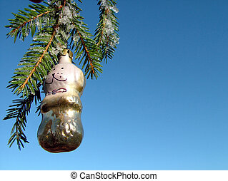 Christmas ornament hangs on the branch of fir tree against...