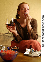 Chocolate and tv 2 - A young woman with a red wine and candy...