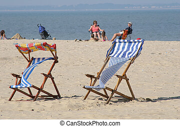 colorful deckchairs on beach - colorful deckchairs on a...