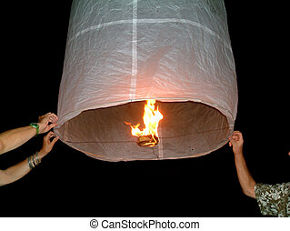 flying lantern - two people holding a flying fire lantern,...