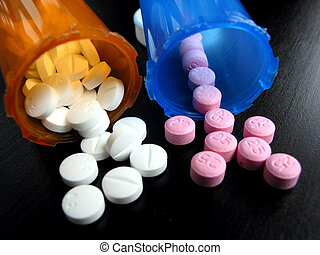 Pills and vials - White and pink pills with pill vials on...