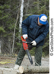 chain saw - active senior cutting a fallen tree with the...
