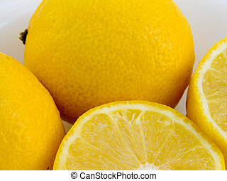 Lemons - Two whole lemons and two half lemons on a white...